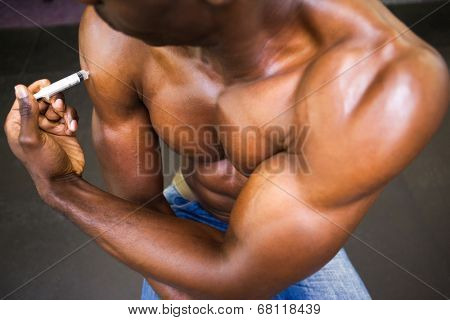 Close up of shirtless muscular man injecting steroids in the gym