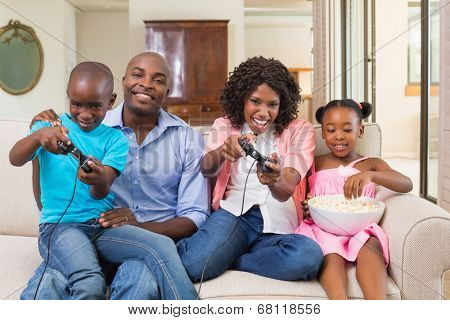 Happy family relaxing on the couch playing video games at home in the living room