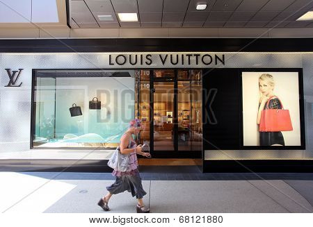 SANTA MONICA, CALIFORNIA - TUES. JUNE 24, 2014: A woman walks past a Louis Vuitton store in Santa Monica, California, on Tuesday, June 24, 2014.