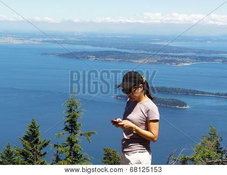 Mature Woman Trying To Use Her Cell Phone While Outdoors Near The Ocean