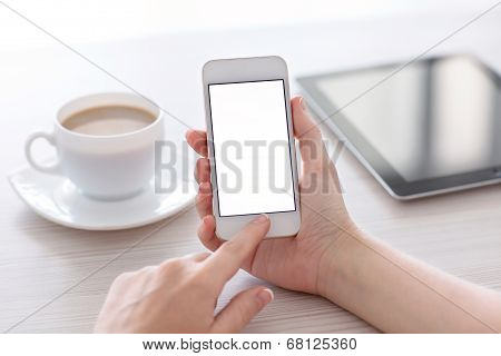 Women Hands Holding The White Phone With Isolated Screen Above The Table