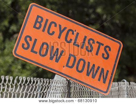 Weathered bicyclists slow down sign in a urban city park.