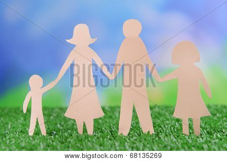 Paper family on green grass, close up