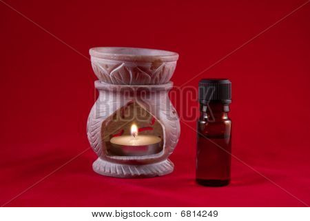 Oil Burner With Tealight Candle And Bottle On Red Background