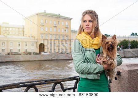 Young woman with small dog on the embarkment.