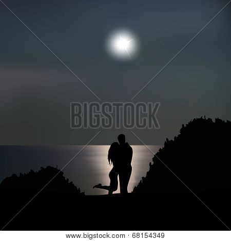 Loving couple on the seashore at night