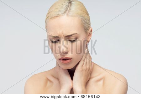 Pain concept. Young woman with touching her throat and head