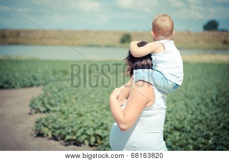 mother holding her child on her neck