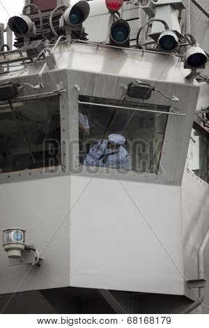 NEW YORK - MAY 22: Reflections in a window of U.S. Navy personnel on the flight deck of the amphibious dock landing ship USS Oak Hill (LSD 51) moored at Pier 92 during Fleet Week NY on May 22, 2014.