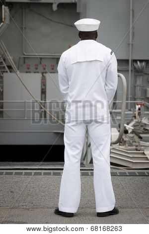 NEW YORK - MAY 22: A sailor stands at the top of the ramp to the flight deck aboard the amphibious dock landing ship USS Oak Hill (LSD 51) moored at Pier 92 for Fleet Week NY on May 22, 2014.