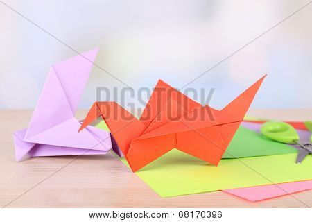 Origami crane and paper on wooden table