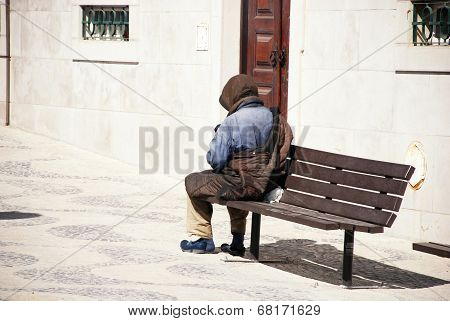 A Homeless Man On A Bench In Lisbon, Portugal.