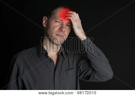 Man With A Sore Head Holding Her Hand. On The Black Background