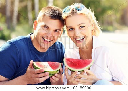 A picture of a young happy couple eating watermelon at the beach