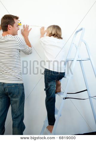Father And His Son Decorating A Room