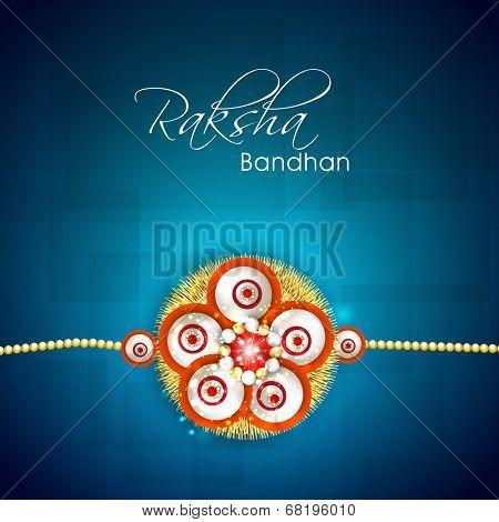 Beautiful floral decorated rakhi on abstract blue background for Happy Raksha Bandhan celebrations.