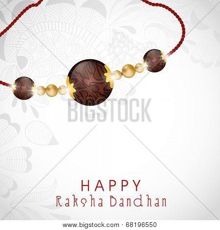 Beautiful rakhi on floral decorated grey background for Happy Raksha Bandhan celebrations.