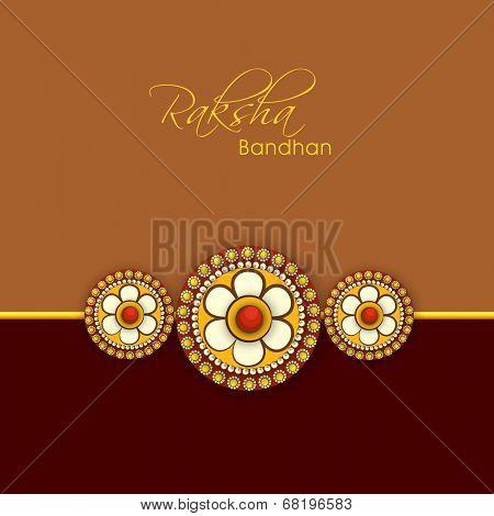 Beautiful rakhi on brown and maroon background for Happy Raksha Bandhan celebrations.