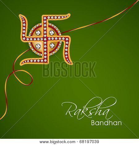 Beautiful rakhi decorated with Swastik on green background for Happy Raksha Bandhan celebrations.