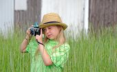 stock photo of fedora  - Little Caucasian girl wearing a fedora and taking a photo with old - JPG