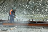 pic of sandblasting  - tradesman sandblasting steel beams for building project - JPG