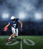 stock photo of incredible  - American Football Player running with the ball in a large stadium - JPG