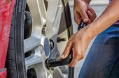 picture of internal combustion  - Woman is changing tire with wheel wrench - JPG
