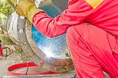 stock photo of pipe-welding  - Welder welding a pipe on a terrain - JPG