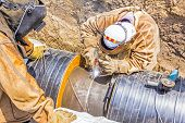 stock photo of pipeline  - Welders welding pipeline together in a teamwork - JPG