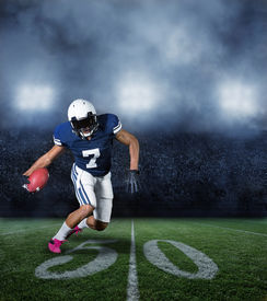 picture of incredible  - American Football Player running with the ball in a large stadium - JPG