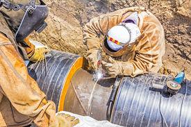 picture of pipeline  - Welders welding pipeline together in a teamwork - JPG