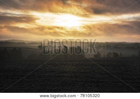 Sunrise over cold foggy autumn morning landscape