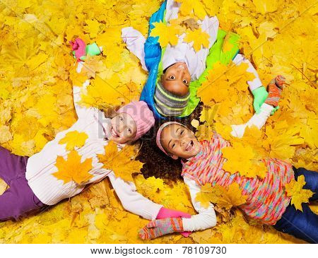 Kids play with autumn maple orange leaves