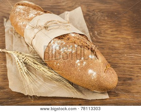 Long Loaf In Paper Packaging With Ears Of Wheat