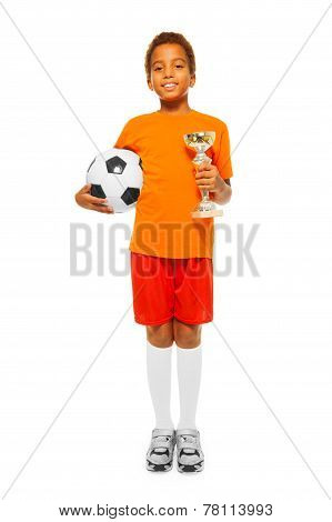 Little African boy holding soccer ball and prize