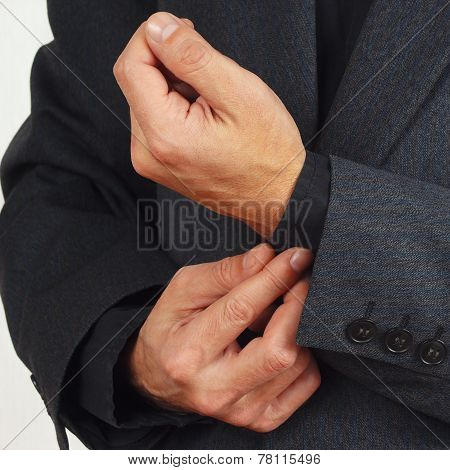 Man unbuttons his sleeve business suit closeup