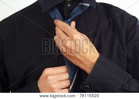 Guy tying his tie over black shirt closeup