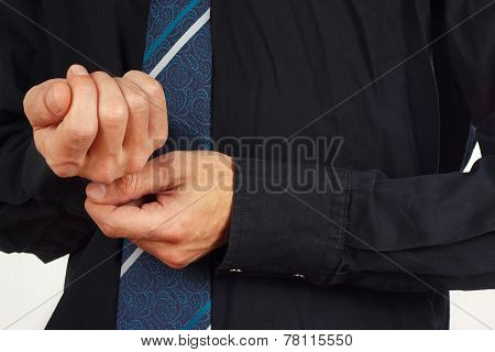 Man fastened the buttons on sleeve black shirt closeup