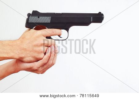 Hands with semi-automatic pistol on white background