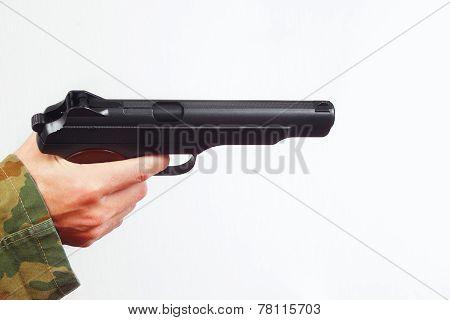 Hand in camouflage uniform with handgun on white background