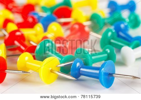 Multicolored pushpins on white desktop closeup