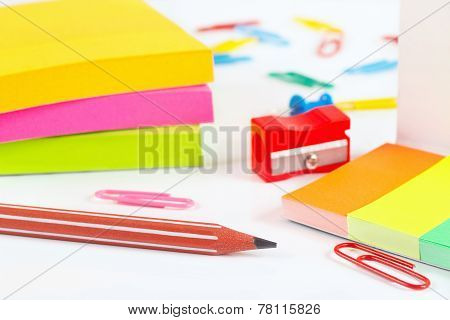 Multicolored stationery supplies on white desktop closeup