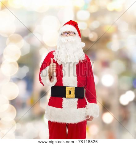 christmas, holidays, gesture and people concept- man in costume of santa claus showing thumbs up over lights background