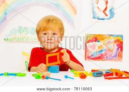 Little blond boy with hacksaw in classroom