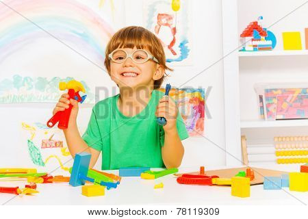 Smart boy in glasses with toy work tools