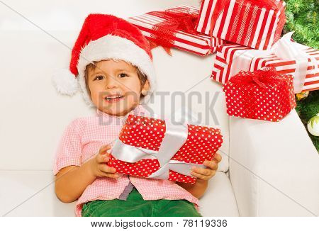 Little boy with pile of Christmas presents