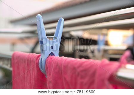 A cloth peg hanging a washed red polyester rag