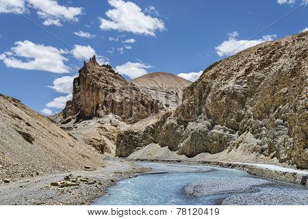 River Flow And Road Nearby In Jagged Mountains