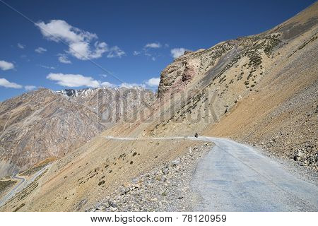 Lonely Biker On Mountain Road
