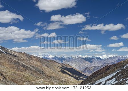Winding Mountain Road Among Snow Capped Summits